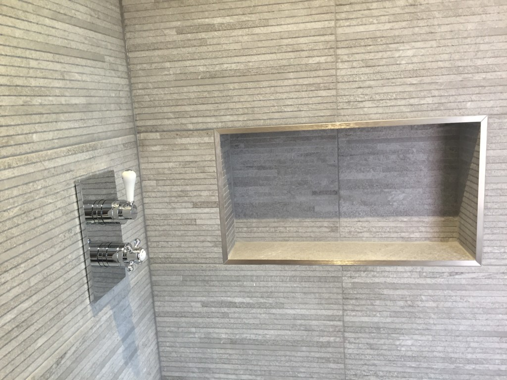 Grey tiles and built in shower caddy